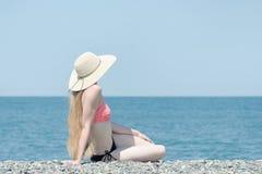 La bella ragazza in un costume da bagno ed in un cappello si siede su una spiaggia su un backgr Immagini Stock Libere da Diritti