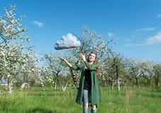 La bella ragazza in un giardino della mela ed in una nuvola blu Fotografie Stock
