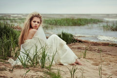 La bella ragazza in un vestito bianco si siede sulla spiaggia nell'ambito delle raffiche di un vento freddo Fotografia Stock