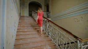 La bella ragazza in un vestito rosso sale le scale video d archivio