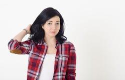 La bella ragazza in una camicia di plaid rossa dei pantaloni a vita bassa corregge l'acconciatura che esamina meditatamente la ma Fotografia Stock Libera da Diritti
