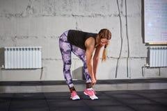 La bella ragazza in una palestra su un fondo di un muro di cemento fissa una gamba su una fasciatura elastica Misura dell'incroci Fotografie Stock