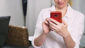 La bella ragazza utilizza uno smartphone cellulare mentre si siede nel salone nella sera Giovane donna sorridente felice stock footage