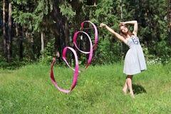 La bella ragazza in vestito, è impegnata in ginnastica ritmica Immagini Stock