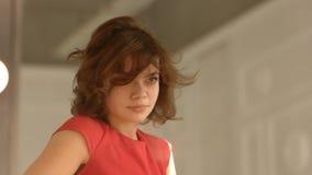 La bella ragazza in vestito da sera rosso ammira in specchio e regola i suoi capelli a casa archivi video