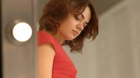 La bella ragazza in vestito da sera rosso ammira in specchio e regola i suoi capelli a casa Dito del piede da dirigersi Donne in  video d archivio