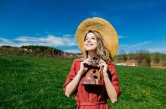 La bella ragazza in vestito rosso ed il cappello si divertono con la macchina fotografica d'annata sul prato in montagne immagini stock libere da diritti