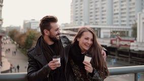 La bella ragazza viene al giovane bello sono risata amichevole dell'abbraccio allegro, tenendo il caffè asportabile Fotografie Stock Libere da Diritti