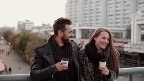La bella ragazza viene al giovane bello sono risata amichevole dell'abbraccio allegro, tenendo il caffè asportabile Fotografia Stock Libera da Diritti