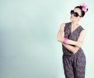 La bella retro ragazza in occhiali da sole con un arco sulla sua testa è nello studio su un fondo blu immagini stock