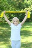 La bella scuola ha invecchiato gli sport dei giochi della ragazza del bambino con una banda del lattice all'aperto nel parco Immagini Stock