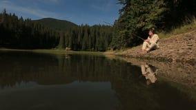 La bella sirena nuda attira il giovane pescatore ingenuo nell'acqua profonda misteriosa del lago Sunevir della montagna dentro stock footage
