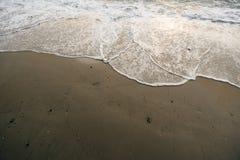 La bella spiaggia spumosa ondeggia alla spiaggia Immagini Stock