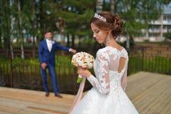 La bella sposa che esamina il mazzo di nozze, sposo alla moda aspetta il suo opposto Fotografia Stock