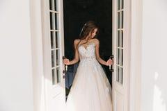 La bella sposa con i capelli lunghi attraenti sta vicino alle porte bianche La giovane donna graziosa in vestito bianco con nozze Fotografia Stock