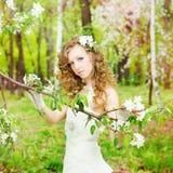 La bella sposa in un vestito bianco nella fioritura fa il giardinaggio fotografie stock libere da diritti