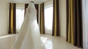La bella sposa in vestito bianco splendido va alla finestra stock footage