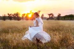 La bella sposa in vestito da sposa si gira al tramonto fotografie stock