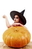 La bella strega dai capelli rossi lancia un incantesimo sopra le zucche Hallowee Fotografie Stock
