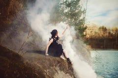 La bella strega della ragazza evoca nel legno Fotografia Stock