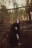 La bella strega della ragazza evoca nel legno Fotografie Stock