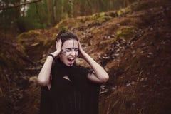 La bella strega della ragazza evoca nel legno immagine stock