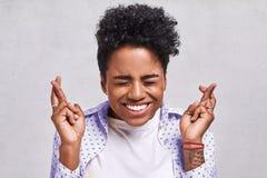 La bella studentessa afroamericana attraversa le dita con grande speranza, ha espressione positiva, posa contro immagine stock libera da diritti