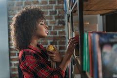 La bella tenuta afroamericana dello studente prenota con la mela e l'esame degli scaffali per libri Fotografia Stock