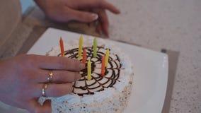 La bella torta di compleanno decorata bianca sta stando sulla tavola a casa archivi video