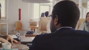 La bella vettura femminile europea di affari dà le indicazioni al CEO afroamericano al gruppo multietnico dell'ufficio che incont stock footage