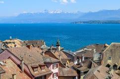 La bella vista al lago geneva ed alle montagne francesi delle alpi con neve completa tramite i tetti di vecchia città di Nyon Immagine Stock Libera da Diritti