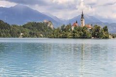La bella vista del lago ha sanguinato con l'isola, la chiesa ed il castello con lo Stol della catena montuosa, Vrtaca, Begunjscic Fotografie Stock