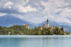 La bella vista del lago ha sanguinato con l'isola, la chiesa ed il castello con lo Stol della catena montuosa, Vrtaca, Begunjscic Immagini Stock