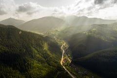 La bella vista panoramica dall'aria alla valle con il villaggio in montagne carpatiche con le nuvole ed il sole rays dentro Fotografie Stock