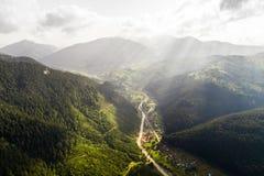 La bella vista panoramica dall'aria alla valle con il villaggio in montagne carpatiche con le nuvole ed il sole rays dentro Immagini Stock Libere da Diritti