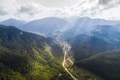 La bella vista panoramica dall'aria alla valle con il villaggio in montagne carpatiche con le nuvole ed il sole rays dentro Fotografia Stock