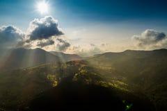 La bella vista panoramica dall'aria alle montagne carpatiche con le nuvole ed il sole rays nella priorità alta Fotografie Stock