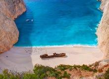 La bella vista sulla spiaggia del naufragio in baia, barche e navi stupefacenti con la gente di nuoto in acqua blu del Mar Ionio, Fotografia Stock Libera da Diritti