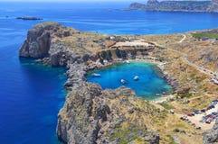 La bella vista sulle rocce di pietra di corallo antiche ed i crogioli bianchi di yacht nel mare blu di Lindos abbaiano sull'isola fotografie stock libere da diritti
