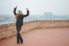 La belle adolescente de sourire écoutent la musique et dansent avec des mains vers le haut d'extérieur photo libre de droits