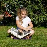 La belle adolescente s'asseyant sur une herbe en parc d'été et lit le livre photographie stock