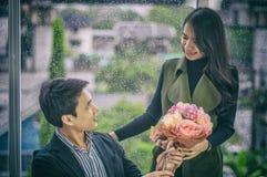 La belle amie offre le bouquet des roses à la jeune séance d'homme d'affaires, pour féliciter des affaires réussies images stock