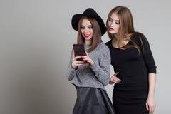 La belle amie vilaine drôle se soulagent au téléphone ayant l'amusement dupant autour dans le studio Photos libres de droits