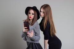 La belle amie vilaine drôle se soulagent au téléphone ayant l'amusement dupant autour dans le studio Image libre de droits