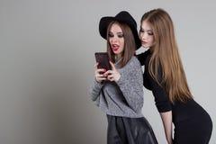 La belle amie vilaine drôle se soulagent au téléphone ayant l'amusement dupant autour dans le studio Image stock