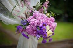 La belle arcade blanche de bas-côté de mariage avec le pourpre fleurit le closeu Photographie stock