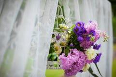 La belle arcade blanche de bas-côté de mariage avec le pourpre fleurit le closeu Photographie stock libre de droits