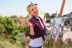La belle artiste blonde de femme peint un coloré Image stock