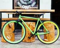 La belle bicyclette de vintage de vitesse fixe vert clair se tient à côté du bar de hippie du ` s de ville photographie stock