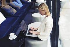 La belle blonde avec les cheveux courts se reposant dans un café dans sa pause de midi, email de balayages image stock